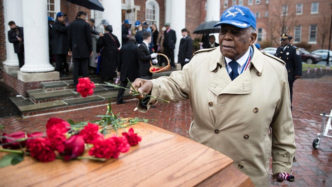 Tuskegee Airman Eugene J. Richardson Jr., places a flower on the casket containing the remains of his comrade John L. Harrison, Jr., after Harrison's a funeral mass at the Chapel of the Four Chaplains in Philadelphia, Friday, March 31, 2017.  Harrison Jr. became one of America's first black military airmen, one of nearly 1,000 pilots who trained as a segregated unit with the Army Air Forces at an airfield near Tuskegee, Ala.