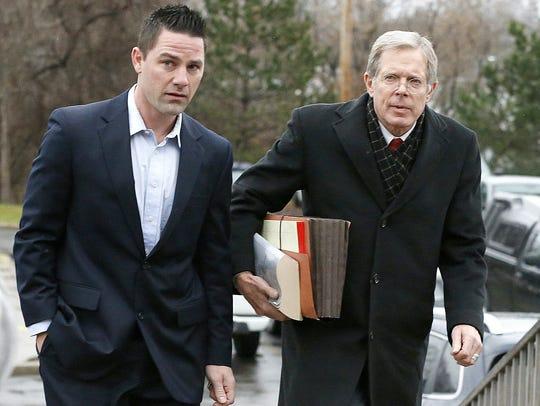 Murder suspect Thomas Clayton, left, walks with his