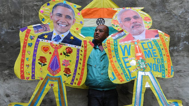 An Indian kitemaker poses with kites adorned with images of President Obama, left, and  Indian Prime Minister Narendra Modi in Amritsar on Jan. 21, 2015.