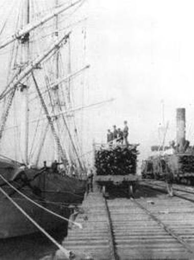 A four-masted schooner docked at the railroad wharf loading lumber in 1898.