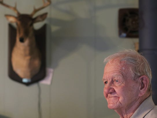 Charles Dowdy walks past a synthetic deer head on the