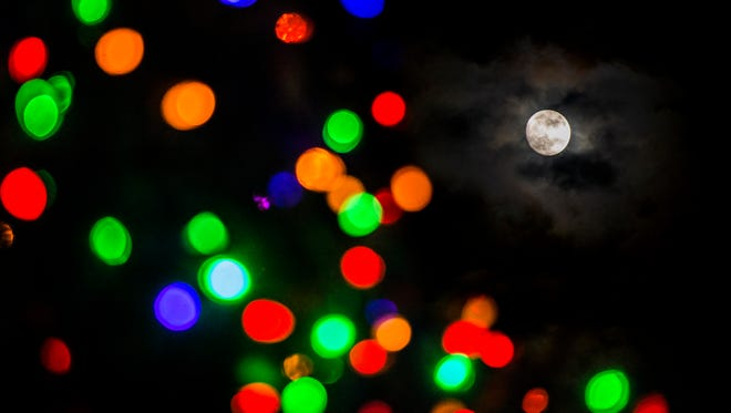 The moon breaks through the fog above the lit Christmas tree in Metro Public Square in Nashville on December 1, 2017.