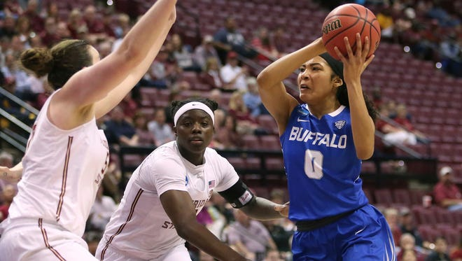 Buffalo's Summer Hemphill cuts between Florida State's Chatrice White, left, and Shakayla Thomas as she drives to the basket in the second round game of the NCAA women's college basketball tournament, Monday, March 19, 2018, in Tallahassee, Fla.