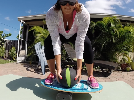 Adding weight, like this medicine ball, is a great way to ramp up a balance-based workout.