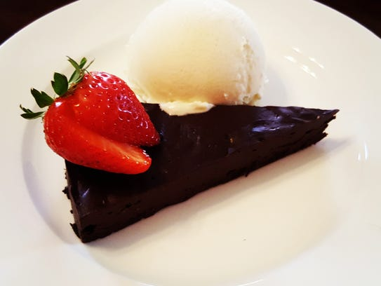 Chocolate flourless torte with vanilla ice cream at