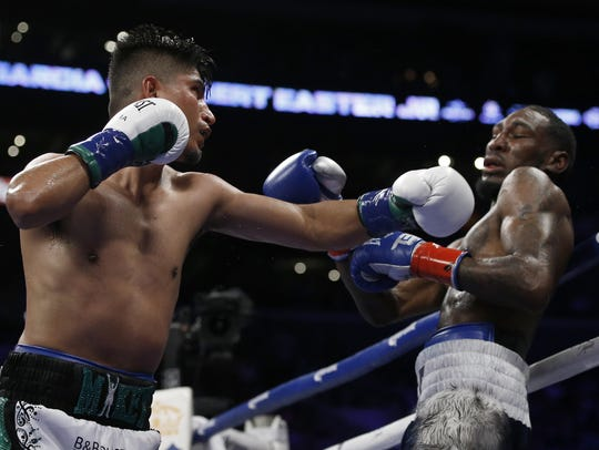 Mikey Garcia, left, hits Robert Easter Jr. with a left during the 12th round of their WBC and IBF lightweight title bout at Staples Center on July 28. Garcia won by unanimous decision.