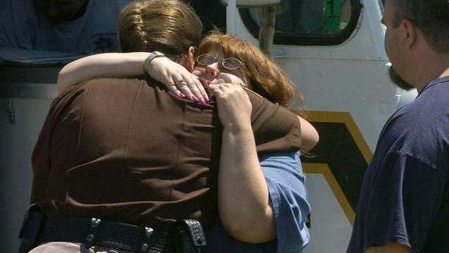 Lisa Holland (center) hugs Ingham County Chief Deputy Vicki Harrison as husband Tim Holland looks on Thursday, July 7, 2005 at the Williamston command center. Police and volunteers continue to search for their 7-year-old son, Ricky.