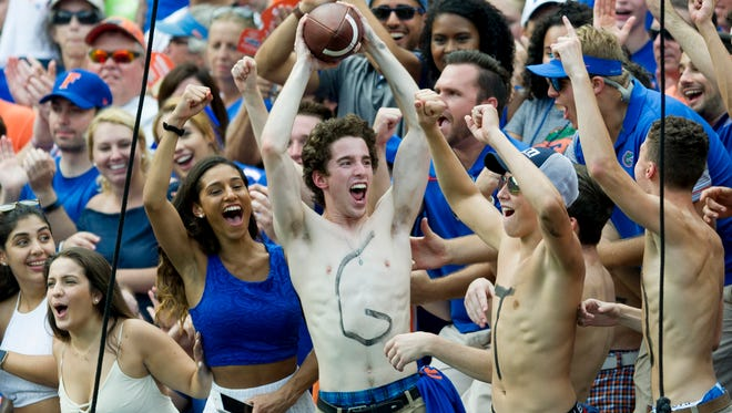 Fans celebrate after the ball flew out of bounds into their section during the Vols-Gators game at Ben Hill Griffin Stadium on Saturday, Sept. 16, 2017.