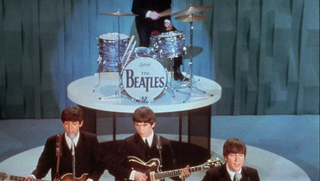 """The Beatles perform on """"The Ed Sullivan Show"""" during the band's first American appearance in New York City on Feb. 9, 1964. From left in the front row are Paul McCartney, George Harrison and John Lennon. Drummer Ringo Starr is at rear."""