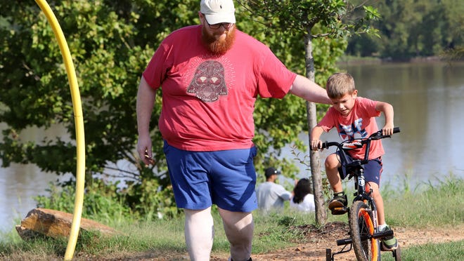 Paul Still helps his son, Asher, 6, take on the bike trails at Riverfront Park, Monday, September 7, running along the Arkansas River.