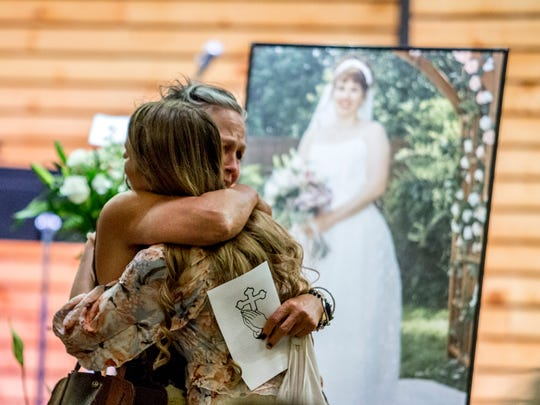 Allison Burnett is embraced by friends and family members