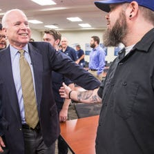 Sen. John McCain (left) talks Monday with Randall Cook, an employee at Able Engineering & Component Services in southeast Mesa. McCain held a town-hall-style meeting where he discussed the migrant crisis at the southwestern border.