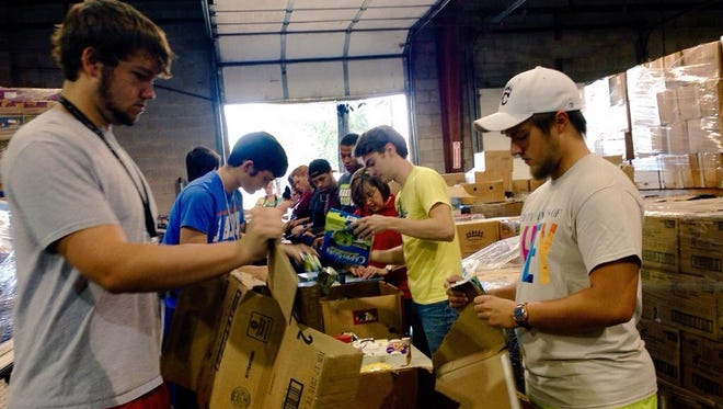 More than 100 incoming freshman at Louisiana College pack backpacks with food for younger Rapides Parish students during a community service project at the Food Bank of Central Louisiana on Friday, the last day of freshman orientation at the private Baptist school in Pineville.