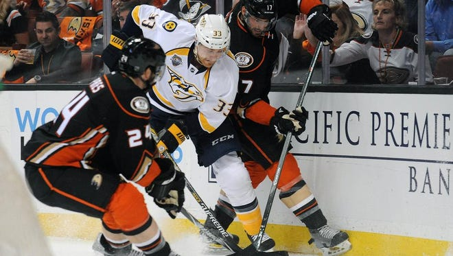 Predators center Colin Wilson (33) plays for the puck against Anaheim Ducks defenseman Simon Despres (24) and center Ryan Kesler (17) during the first period.