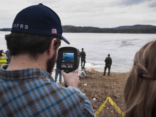 A member of the Charlotte Volunteer Fire and Rescue Squad uses a thermal imaging camera at Shelburne Pond in Shelburne on Wednesday, March 9, 2016, after a Fish and Game warden went through the ice while investigating a hole in the ice.  After he was rescued, authorities discovered a body under the water.