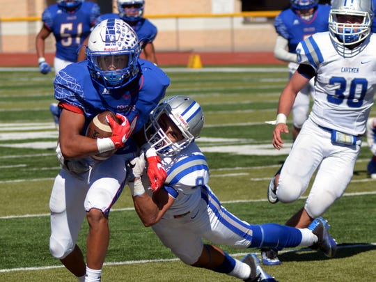 Las Cruces High's Ivan Molina drags a Carlsbad player as he makes a nice gain during Saturday's game at Field of Dreams.