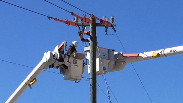 FPL workers reconnect power lines over Summerlin Road that had been affected by high winds.