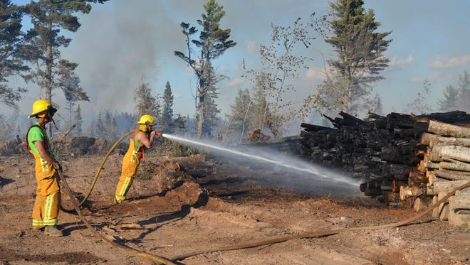 In a July 30, 2015 photo provided by the Michigan Department of Natural Resources,  firefighters from the Champion Township Fire Department pour water on a burning deck of logs at the Marquette County Road 601 fire in Humboldt Township, Mich. Crews in Michigan's Upper Peninsula are making progress in battling the wildfire that's been fueled by warm weather and strong winds. The DNR says the wildfire was about 95 percent contained on Friday morning.