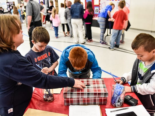 Students of Garfield elementary fill out and cast their votes for the best presentation during the Garfield Elementary Biography Fair on Wednesday.