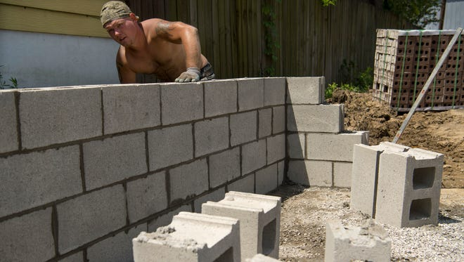Jason Lamar, an employee with Lockhart Masonry, strikes joints on the foundation of a Habitat for Humanity home as he nears the end of his work day Thursday morning. Two workers had already been excused for the day after showing signs of heat exhaustion in the unforgiving heat and humidity.