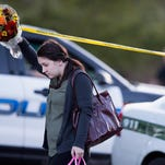A woman navigates crime scene tape as she holds flowers on the campus of Umpqua Community College as it reopened Monday in Roseburg, Oregon.