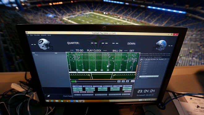 A monitor above Ford Field shows statistics and movement for players and officials Aug. 13, 2015.