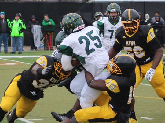 King defenders Jeremiah Thomas (32) and Cepeda Phillips (10) put the clamps on Groves running back Ernest Allen (25).