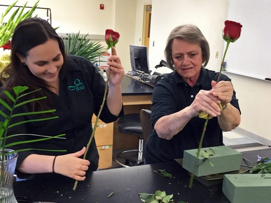 New Mexico State University Floriculture Program students Hanah Rheay, left, and Donna Farmer prepare roses for a flower arrangement.