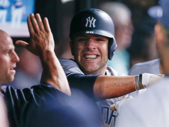 New York Yankees' Austin Romine celebrates in the dugout