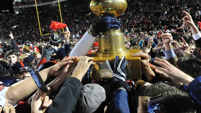 Ole Miss fans and players celebrate with the Egg Bowl trophy after beating MSU 41-24 in Oxford in 2012.