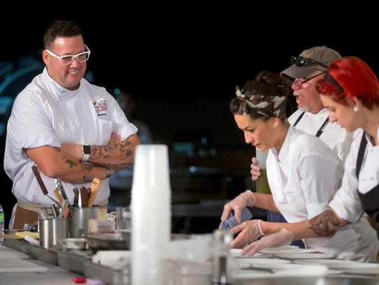 Graham Elliot, left,  watches his staff plate dinner