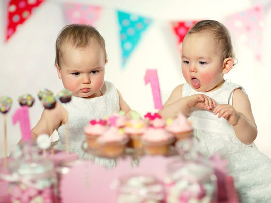 Beautiful happy twins baby on first birthday background.