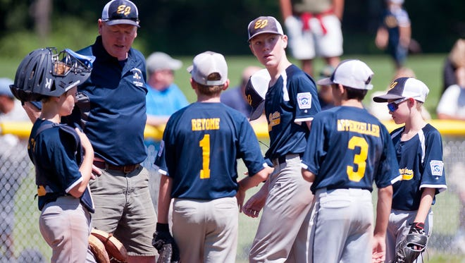 Essex Junction meets at the mound before the final out of their 10-0 win over Brattleboro in Saturday's 11-12-year-old Little League baseball state championship game in Essex.