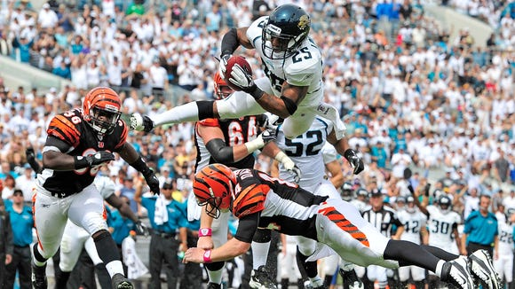 Quarterback Andy Dalton #14 of the Cincinnati Bengals makes the tackle after throwing an interception to Dwight Lowery #25 of the Jacksonville Jaguars during play at EverBank Field on October 9, 2011 in Jacksonville, Florida.  (Photo by Grant Halverson/Getty Images)