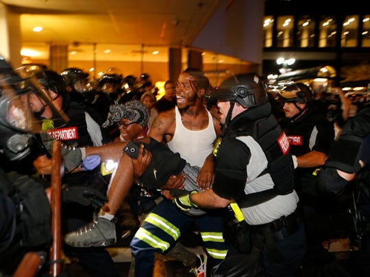 Police and protesters carry a seriously wounded protester into the parking area of the the Omni Hotel during a march to protest the police shooting death of Keith Scott turned violent Sept. 21, 2016 in Charlotte, N.C. The wounded man was initially reported to have died, but city officials later said he was in critical condition.  Scott, who was black, was shot and killed at an apartment complex near UNC Charlotte by police officers, who say they warned Scott to drop a gun he was allegedly holding. A state of emergency has been declared in the city.