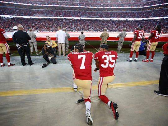 Colin Kaepernick, left, and Eric Reid of the San Francisco 49ers kneel during the anthem prior to the game against the Los Angeles Rams at Levi Stadium on September 12 in Santa Clara, California.