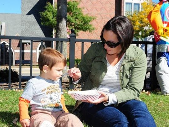 Two-year-old Luke Kowalski tries his first potato pancake as his mom Tina serves up the delicious Polish food that was on hand at the Farmington Farmers Market.