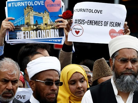 People hold placards during a gathering of representatives of the Muslim south of London Bridge in London, on June 7, 2017, following the June 3 terror attack on London Bridge and Borough Market. British police confirmed on June 7 that the death toll from last weekend's terror attack in London had risen from seven to eight, after announcing a body had been recovered from the River Thames.