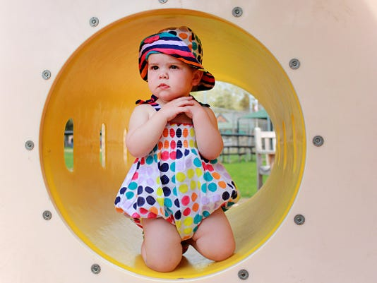 A fourteen month old baby girl in a playground setting, survey's her surroundings as she pauses for