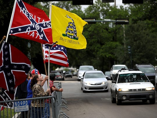 Protesters hold flags across the street from the Jefferson Davis monument on May 4 in New Orleans.