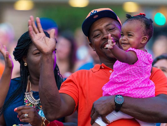 Afro American man and his daughter. People gathered for the