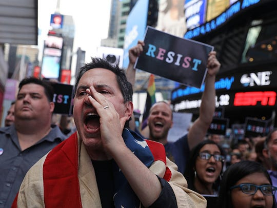 Dozens of protesters gather in Times Square near a