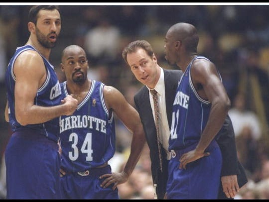 Coach Dave Cowens of the Charlotte Hornets looks over his team, center Vlade Divac (left), guard Tony Smith (center) and guard Glen Rice during a game against the Los Angeles Lakers at the Great Western Forum in Inglewood, California, on Jan. 8, 1997.