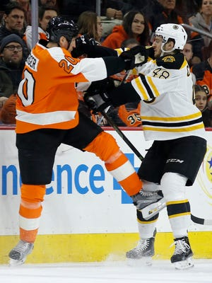 Philadelphia Flyers' R.J. Umberger, left, and Boston Bruins' Colin Miller collide during the first period of Monday's game.