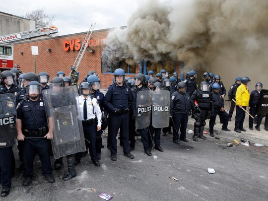 Police stand in front of a burning store in Baltimore