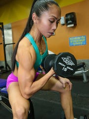 Rhea Macaluso does her arm curls during training at Paradise Fitness Center in Hagåtña on Aug. 18.