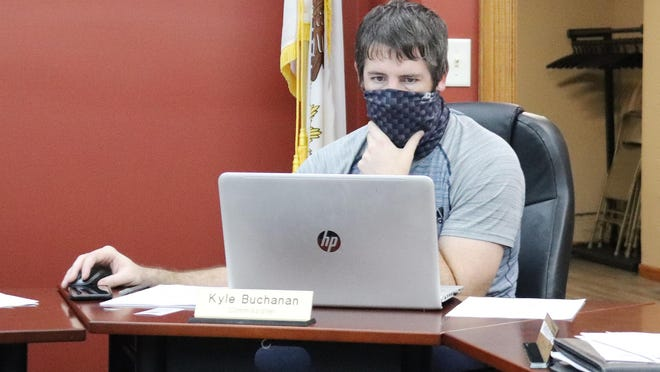 Following protocol, a masked Commissioner Kyle Buchanan looks over information during Tuesday's Chenoa City Council meeting.