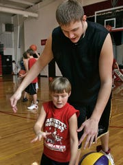 Carly Jacobs, 8, engages her brother,  Jordan Eglseder, during a break in basketball practice at Bellevue Marquette in 2006. Eglseder shared his story of academic challenges with the Register.