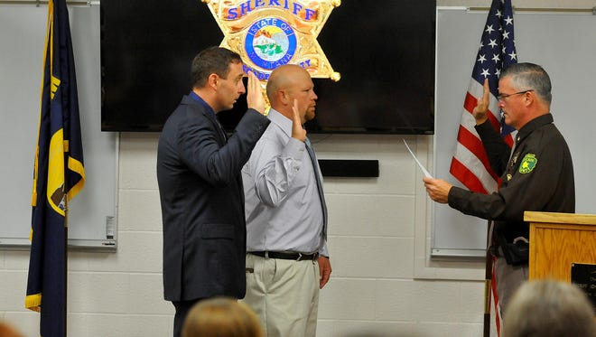 Cascade County Sheriff Bob Edwards, right, swears in two new deputies, Anthoney Gilbert, left, and Justin Hader, on Monday morning at the Cascade County Sheriff's Office.