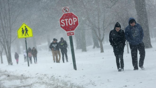 Students from Western International High School in southwest Detroit walk home on Scotten Street after being dismissed early because of the snow on Wednesday, Dec. 13, 2017.